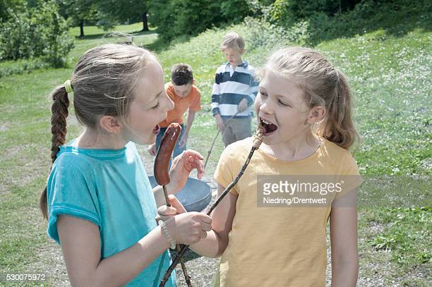 Friends feeding sausage to each other, Bavaria, Germany