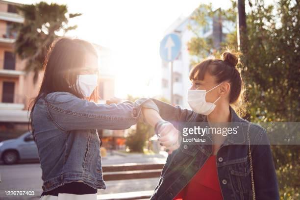 les amis se rencontrent enfin à nouveau dans les rues, tenant la main portant des gants de protection - éviter de se serrer la main photos et images de collection