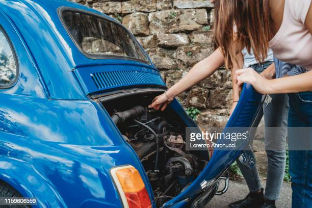 friends fixing stalled car in countryside - vintage auto repair stock pictures, royalty-free photos & images
