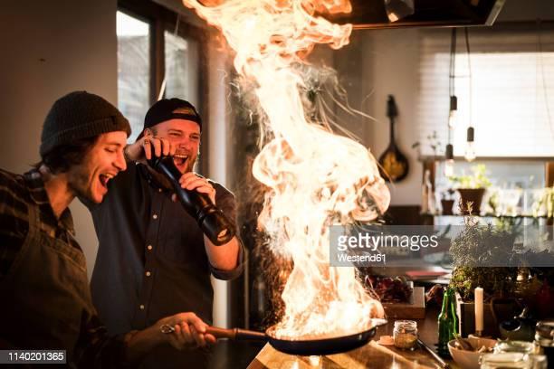 friends flambeing food in a pan, producing a big flame - verzückt stock-fotos und bilder