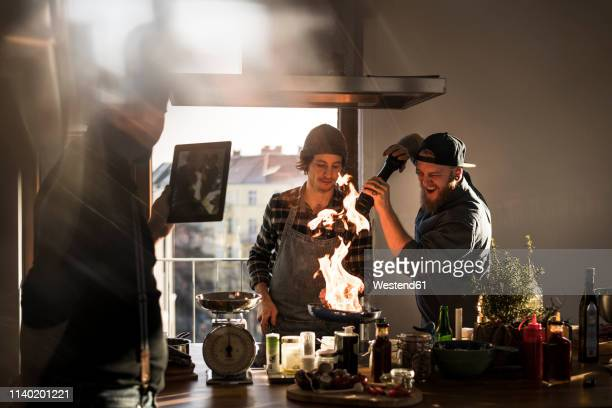 friends flambeing food in a pan, producing a big flame, while friend is filming - tres personas fotografías e imágenes de stock