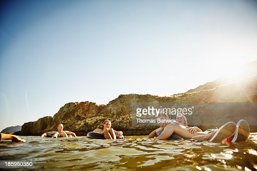 Friends floating on inner tubes in river laughing