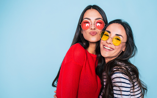 Friends forever. Two cute lovely girl friends in sunglasses posing with smile on blue background 1029231320