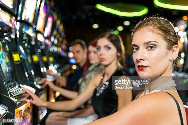 friends gambling in the casino on slot machines - teen pokies stock photos and pictures