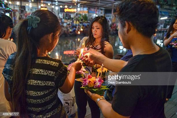 Friends gather to release floating offerings during Loy Kratong festival in Bangkok, Thailand