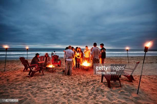 friends gathered around fire on beach on summer evening - キャンプファイヤー ストックフォトと画像