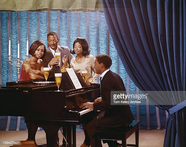 Friends gathered around man playing piano