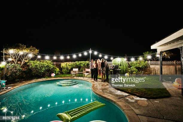 Friends gathered by backyard pool during party on summer evening