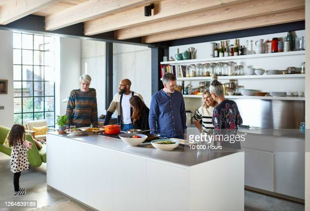 friends gathering in open plan kitchen for lunch - social gathering stock pictures, royalty-free photos & images