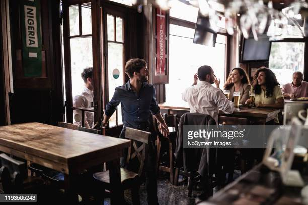 friends gathering in pub, watching a soccer game - medium group of people stock pictures, royalty-free photos & images