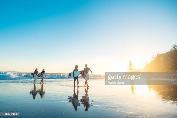 friends getting out of the water at sunset after surfing - gold coast queensland stock pictures, royalty-free photos & images