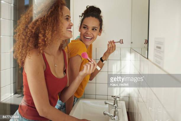 friends getting ready in front of mirror in bathroom - tienermeisjes stockfoto's en -beelden