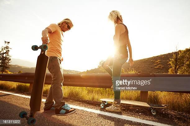 Friends getting ready to start longboarding.