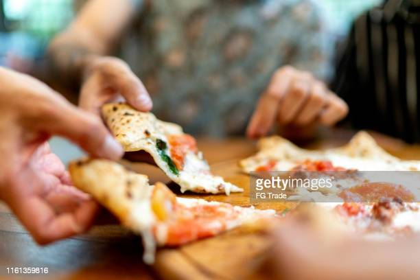 friends getting slices of pizza, using hands - pizza stock pictures, royalty-free photos & images