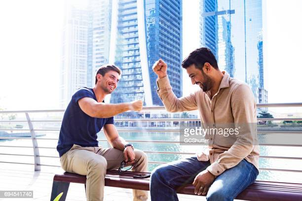 friends giving each other a fist bump after meeting each other after work - fist bump stock pictures, royalty-free photos & images