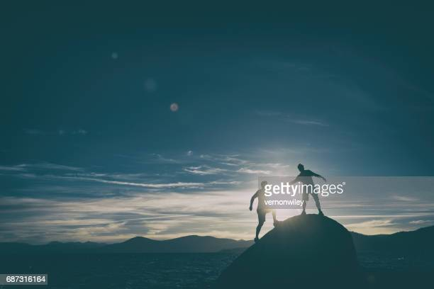 friends giving each other a hand in the mountains - practicing stock pictures, royalty-free photos & images