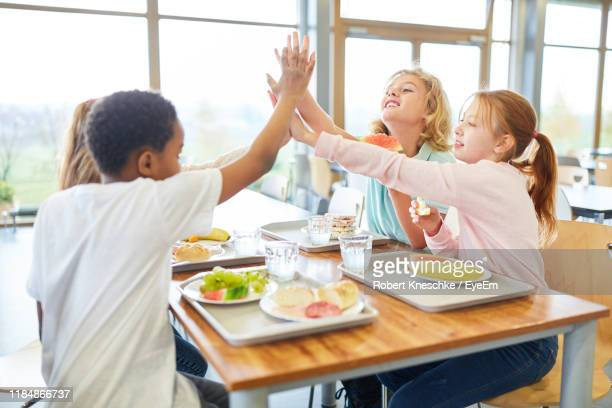 friends giving high-fives sitting at table in school - cantine photos et images de collection