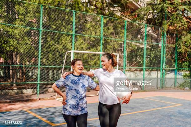 vrienden die naar huis gaan door na een goede voetbalspel te chatten - voetbal teamsport stockfoto's en -beelden
