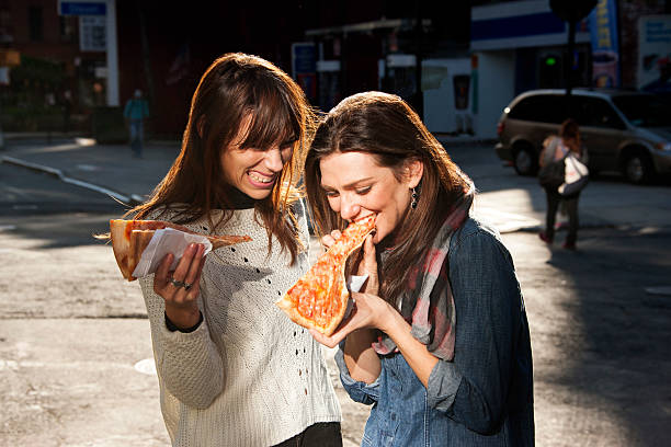 Friends grabbing a slice of pizza on the go