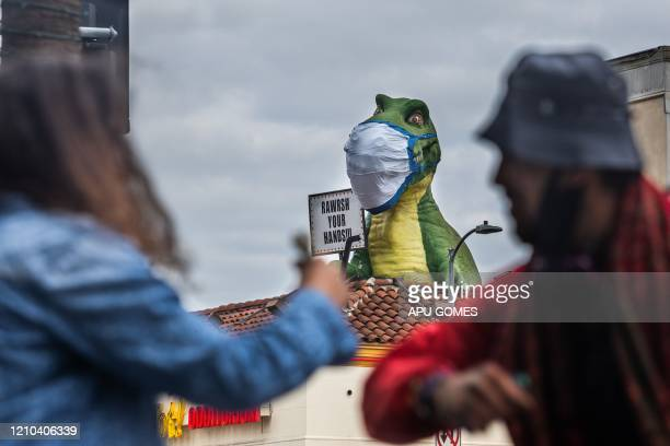Friends greet each other with a tap of the elbow next to a dinosaur atop the Ripley's Believe It or Not Odditorium wearing a face mask next to a sign...