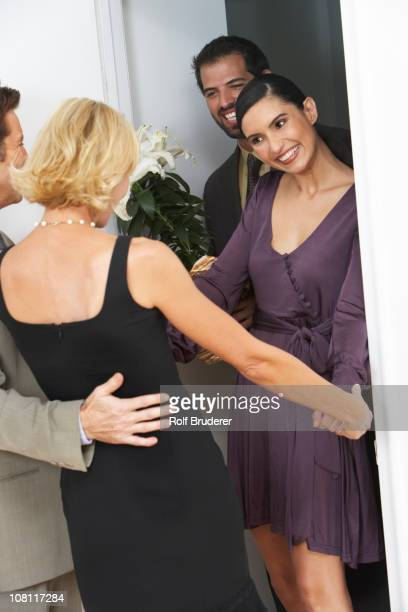 Friends greeting couple arriving for party