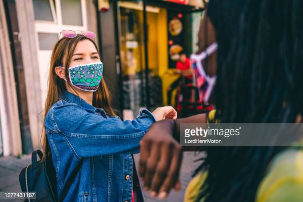 friends greeting during covid-19 pandemic, elbow bump - bumpy stock pictures, royalty-free photos & images