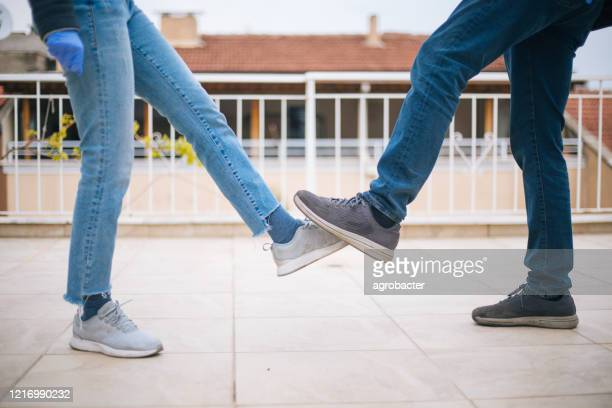 friends greeting during covid-19 pandemic - elbow bump stock pictures, royalty-free photos & images