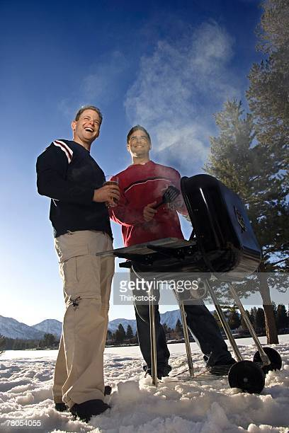 Friends grilling outdoors in snow