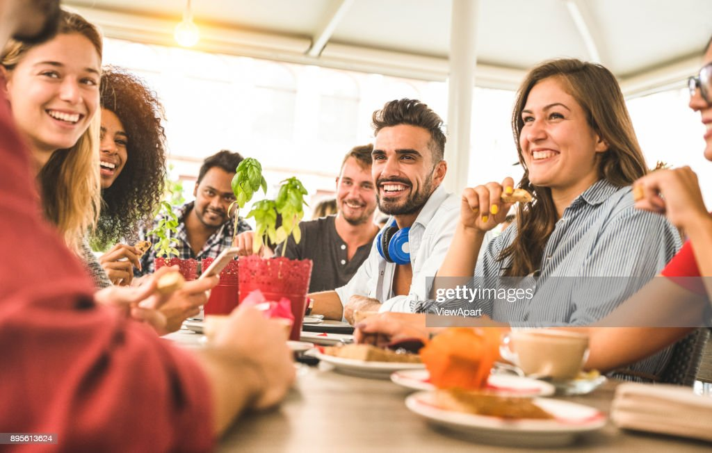Friends group drinking cappuccino at coffee bar restaurant - People talking and having fun together at fashion cafeteria - Friendship concept with happy men and women at cafe - Warm vintage filter : Stock Photo