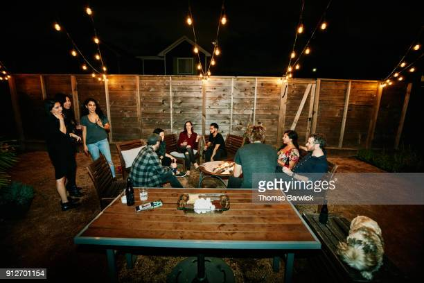 friends hanging out around fire in backyard after dinner party on summer evening - table after party stock pictures, royalty-free photos & images