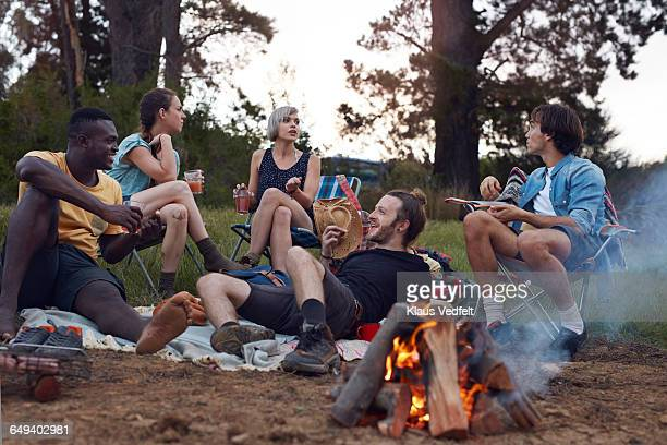 friends hanging out at campsite with bonfire - non urban scene stock pictures, royalty-free photos & images