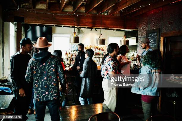 friends hanging out in bar - happy hour stock pictures, royalty-free photos & images