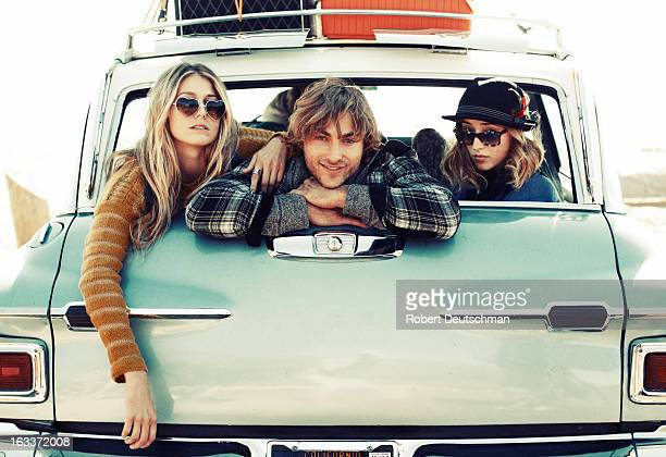 Friends hanging out in the back of a car.