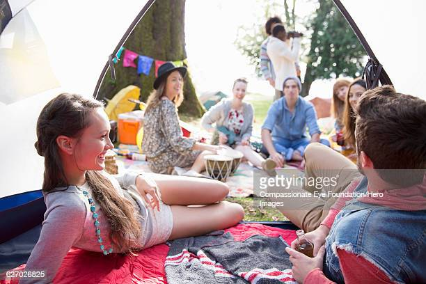 """friends hanging out relaxing at music festival - """"compassionate eye"""" stock pictures, royalty-free photos & images"""