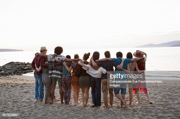 """friends hanging out relaxing on beach - """"compassionate eye"""" stock pictures, royalty-free photos & images"""
