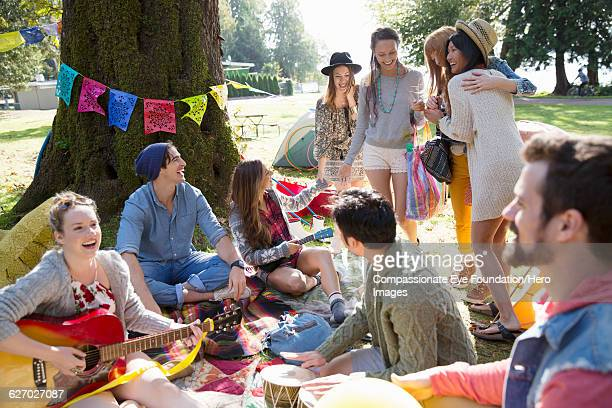 Friends hanging out relaxing on blanket in park