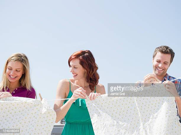 Friends hanging sheets on clothesline