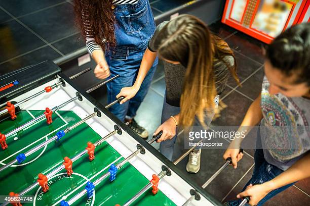 Friends have fun on the game room playing foosball