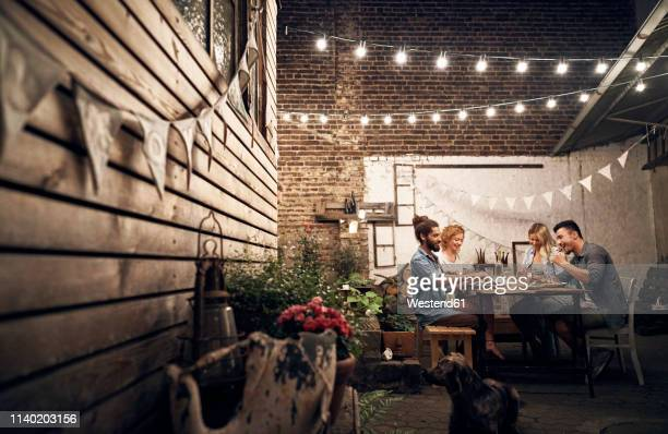 friends having a barbecue in the backyard, eating together - abenddämmerung stock-fotos und bilder