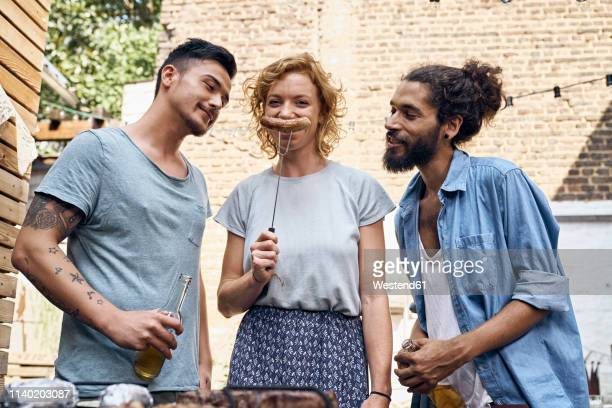 friends having a barbecue n the backyard, preparing meat on a grill - funny bbq stock pictures, royalty-free photos & images