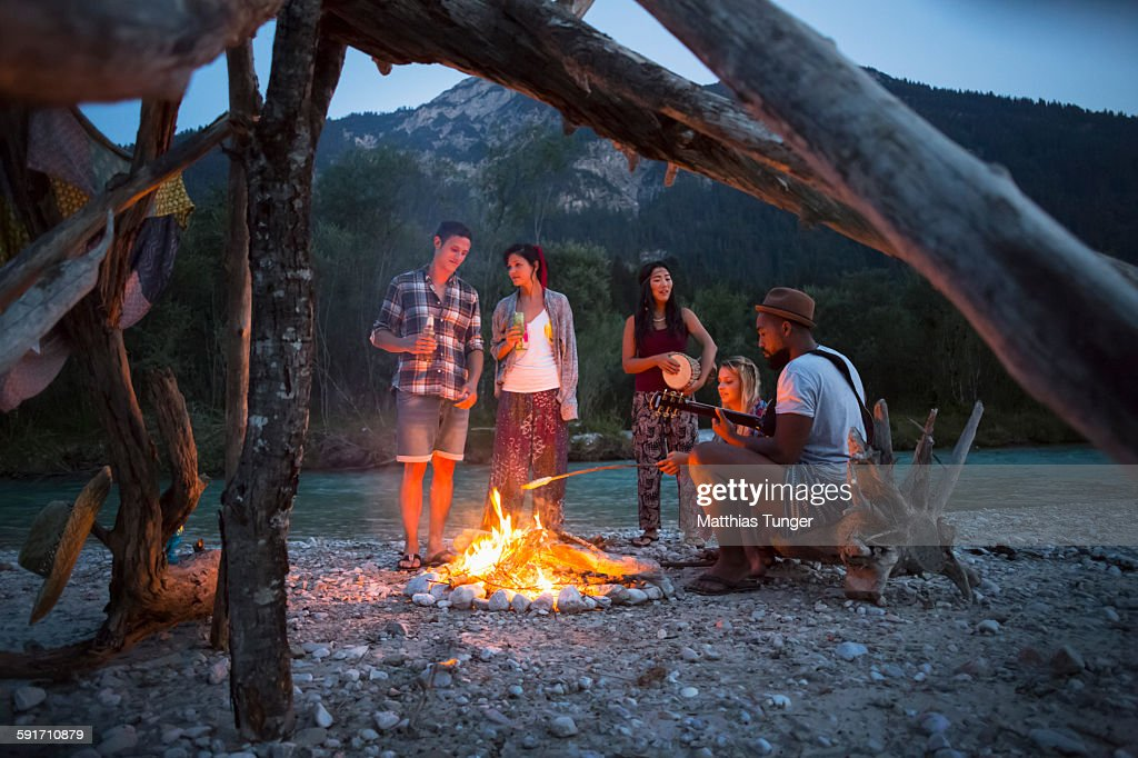 Friends having a campfire in the nature at sunset : Stock-Foto
