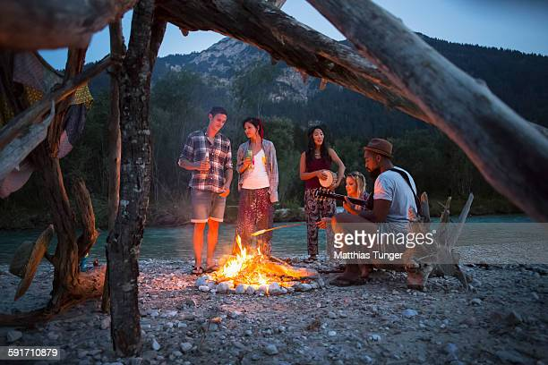 friends having a campfire in the nature at sunset - lagerfeuer stock-fotos und bilder