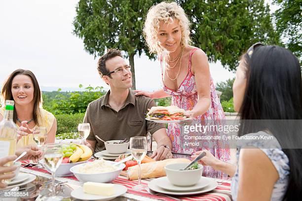 "friends having a dinner party on a patio. - ""compassionate eye"" fotografías e imágenes de stock"