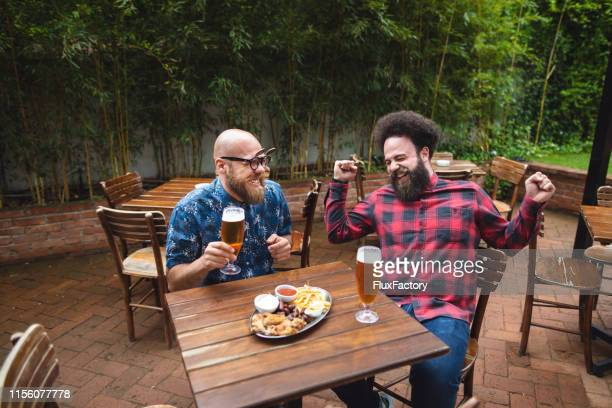 friends having a good time in a bar - best sunglasses for bald men stock pictures, royalty-free photos & images