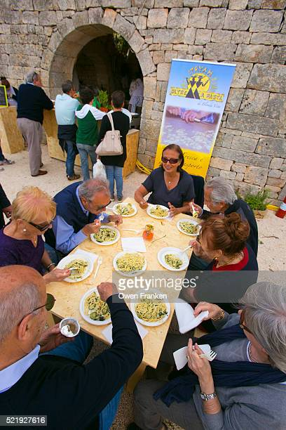 friends having a meal at a farmers' products fair, Locorotondo, Puglia, Italy