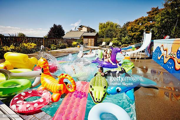 friends having a pool party with inflatable toys - pool party stock pictures, royalty-free photos & images