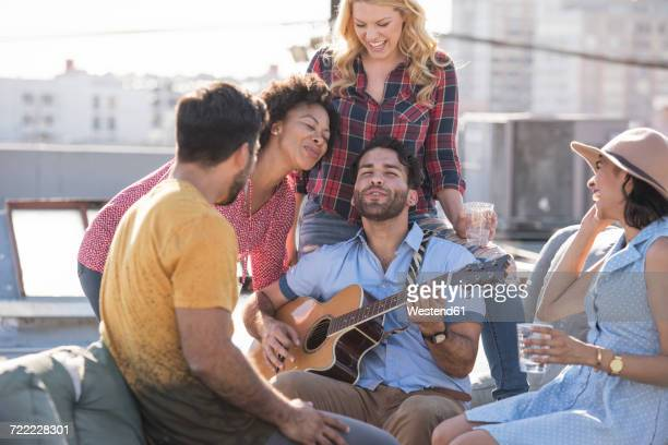 friends having a rooftop party and playing guitar - plucking an instrument stock pictures, royalty-free photos & images