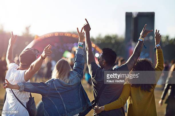 friends having arms in the air in front of stage - festival or friendship not school not business stock photos and pictures