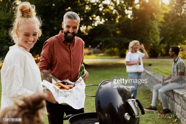 friends having barbecue in park - garden party stock pictures, royalty-free photos & images