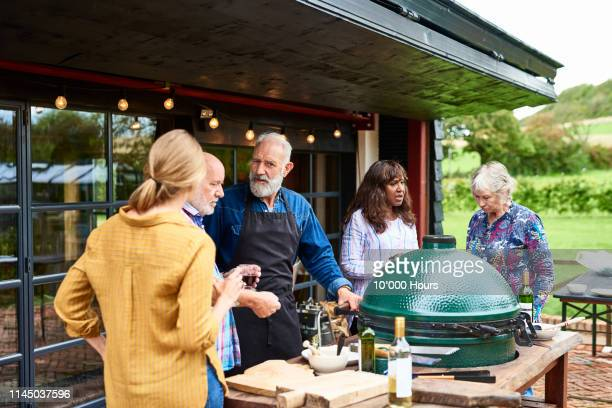 friends having bbq on terrace in rural setting - stepfamily stock photos and pictures